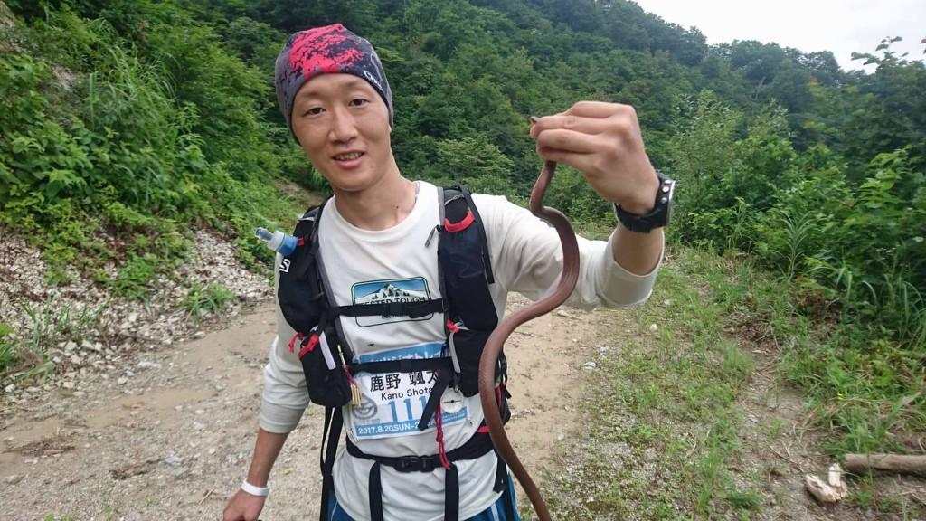 やにわにヘビを捕まえて観察する鹿野さん。